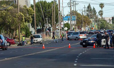 At left, investigators study San Jose police officer Michael J. Katherman's motorcycle as it lies on Commercial Street near Horning Street after a minivan, center, hit the motorcycle officer in San Jose, Calif., on Tuesday, June 14, 2016. Katherman was killed in the accident. (LiPo Ching/Bay Area News Group)