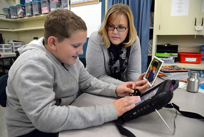"""With the help of Kristin Schaefer, a teacher at the Morgan Autism Center, Hayden Neff, 11, types on his """"talker,"""" a voice augmentation device that helps him articulate answers on Thursday, Nov. 7, 2013, in San Jose, Calif. (Karl Mondon/Bay Area News Group)"""