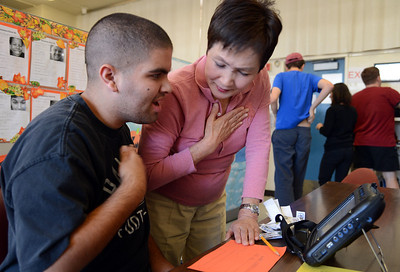 With the help of Romi Kurahashi, an instructional aide at the Morgan Autism Center, student Giancarlo Aiuto, 21, types on a voice augmentation device that helps him communicate on Thursday, Nov. 7, 2013, in San Jose, Calif. (Karl Mondon/Bay Area News Group)