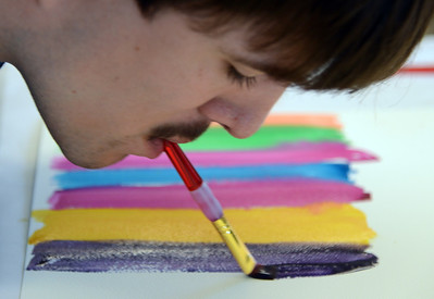 Kolya works on art project at the Morgan Autism Center, Wednesday, Nov. 6, 2013 in San Jose, Calif. The Russian-born, 22-year-old has no arms but he's learned how to use his mouth to paint and has become a prolific artist. (Karl Mondon/Bay Area News Group)