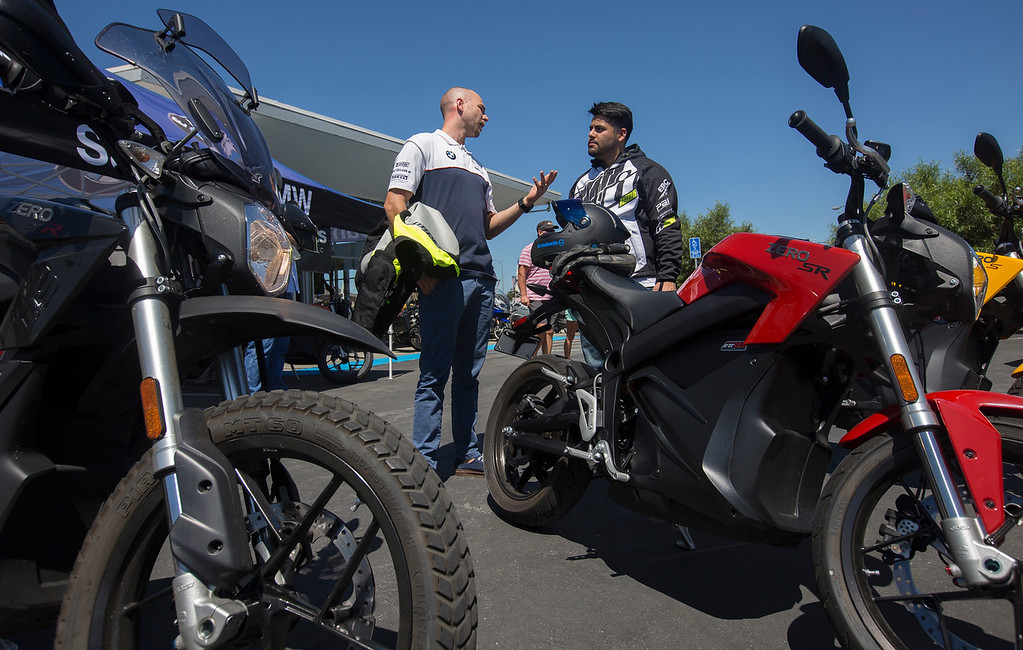 . San Jose BMW manager, Willie Hodgson, left, talks with Franco Rodriguez, of Palo Alto, as Zero Motorcycles holds a demonstration event at San Jose BMW in San Jose, Calif., Saturday, June 24, 2016. There is a burgeoning electric motorcycle market, which includes one of the major players, Zero Motorcycles of Scotts Valley.  (Patrick Tehan/Bay Area News Group)