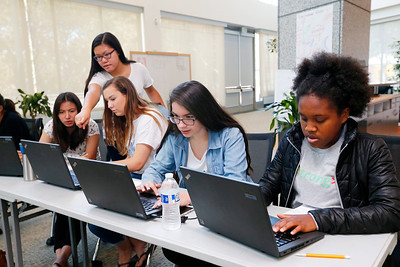 Teaching assistant, Maggie Chang, 17, standing, helps a group work on their coding projects during a summer program at Adobe Systems in San Jose, Calif., on Tuesday, June 28, 2016. Sitting left to right are students, Gaby Quan, 16, Kristen Miller, 17, Edith Gonzalez, 16, and Hannah Leonard, 16. There has been a growth in coding camps to get girls interested in learning to write code. (Photo by Gary Reyes/Bay Area News Group)