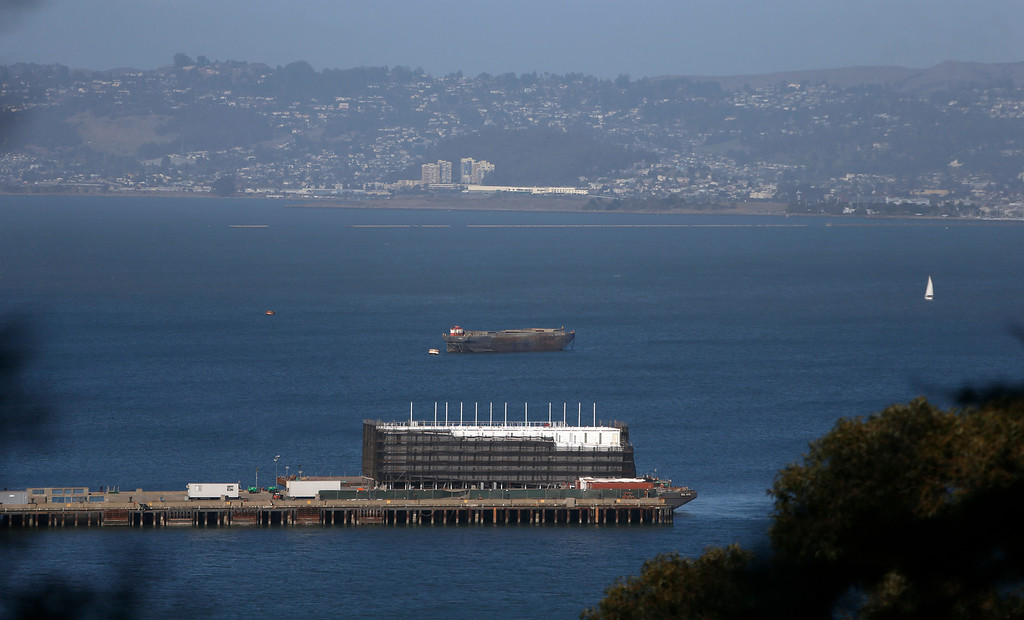 . Speculation is rampant about the top-secret, four-story structure that\'s been erected atop a huge barge, now sitting next to a pier at Treasure Island in the middle of San Francisco Bay. Neither Google nor the mysterious company listed as the barge\'s owner have said a peep in public since the tech news site CNET linked the hush-hush project to the Internet search giant last week.  Photographed along Pier 1 in Treasure Island, Calif. on Monday, October 28, 2013.  (Nhat V. Meyer/Bay Area News Group)