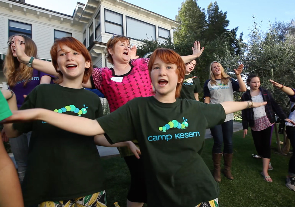 . Abby, right,  and Emma Lauter, with their mother Jennifer, center, sing during a reunion of Camp Kesem participants Sunday afternoon, Nov. 1, 2015, in Stanford, Calif. The twins joined Camp Kesem, a community support group for children of cancer patients, when their mother was battling breast cancer. (Karl Mondon/Bay Area News Group)