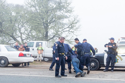 Will Parrish being dragged to the side of the road to allow traffic to resume. (Sara Grusky has been zip tied and is awaiting placement in the patrol car. Photo by Steve Eberhard