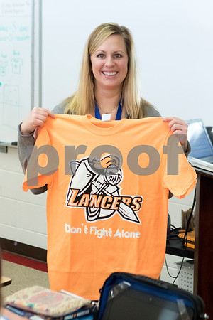 "Sam Buckner for Shaw Media.<br /> Marissa Dobie holds up her shirt which reads ""Lancers don't fight alone"" in support of her son Jake who has been diagnosed with Leukemia on Thursday February 1, 2018."