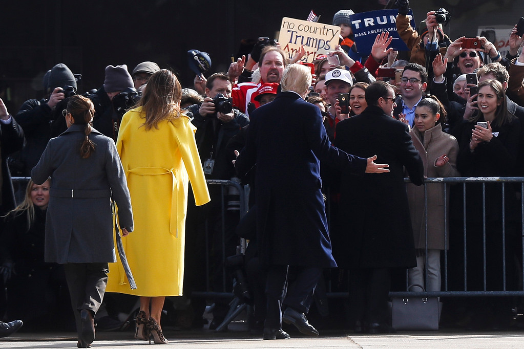 . President Donald Trump, center, greets supporters alongside first lady Melania Trump as they arrive at Cincinnati Municipal Lunken Airport, Monday, Feb. 5, 2018, in Cincinnati. (AP Photo/John Minchillo)