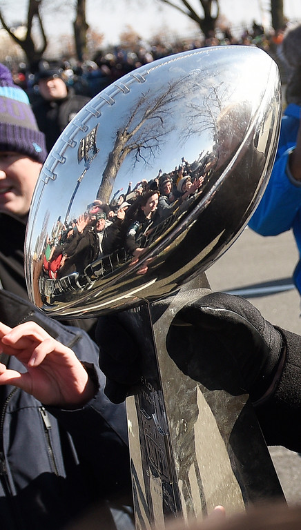 . Philadelphia Eagles NFL football head coach Doug Pederson carries the Lombardi Trophy past fans along the parade route during the Super Bowl LII victory parade, Thursday, Feb 8, 2018, in Philadelphia. (AP Photo/Michael Perez)