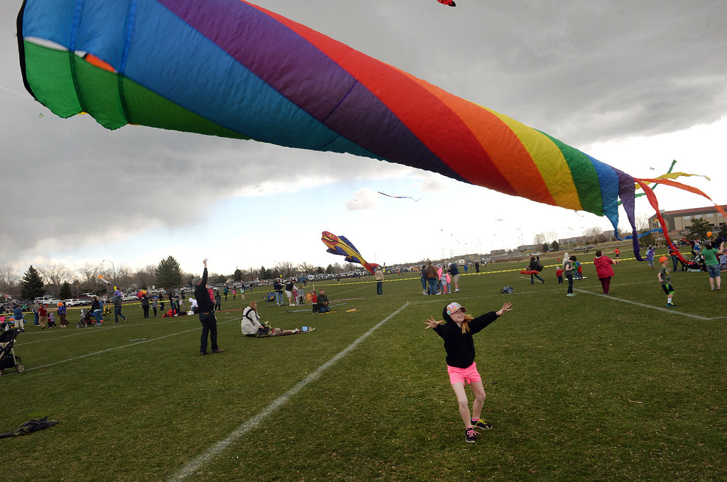 . Freja Hampton, 7, of Westminster, reaches up for her families kite as it takes flight during the 12th annual Arvada Kite Festival held at the Stenger soccer complex in Arvada, Colorado, on April 6, 2014.  Hundreds of people braved cold temperatures , some rain and gusty winds to fly their kites  of all different sizes, shapes, and colors.  Activities included kite making classes and competitions for highest kite, smallest kite, largest kite and most visually appealing kite.  (Photo By Helen H. Richardson/ The Denver Post)