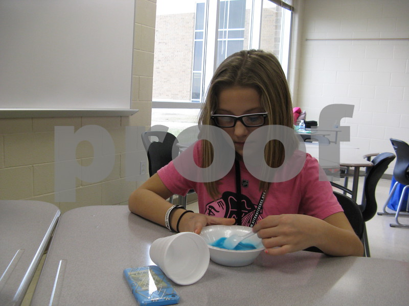 Nevaeh Slayton, 10, makes blue slime during a session at the Students Involved with Technology Conference on Saturday at DeKalb High School.