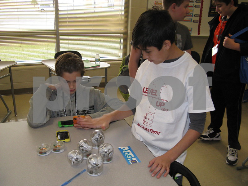 Josh Melms (left), 12, and David Sandoval, 11, try to get their robots to work during the Students Involved with Technology Conference on Saturday at DeKalb High School.