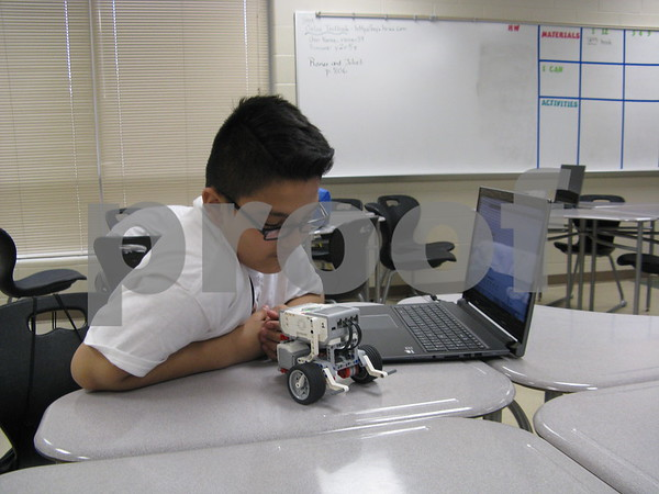 Rodrigo Pena, 10, programs a Lego robot during the Students Involved with Technology Conference on Saturday at DeKalb High School.