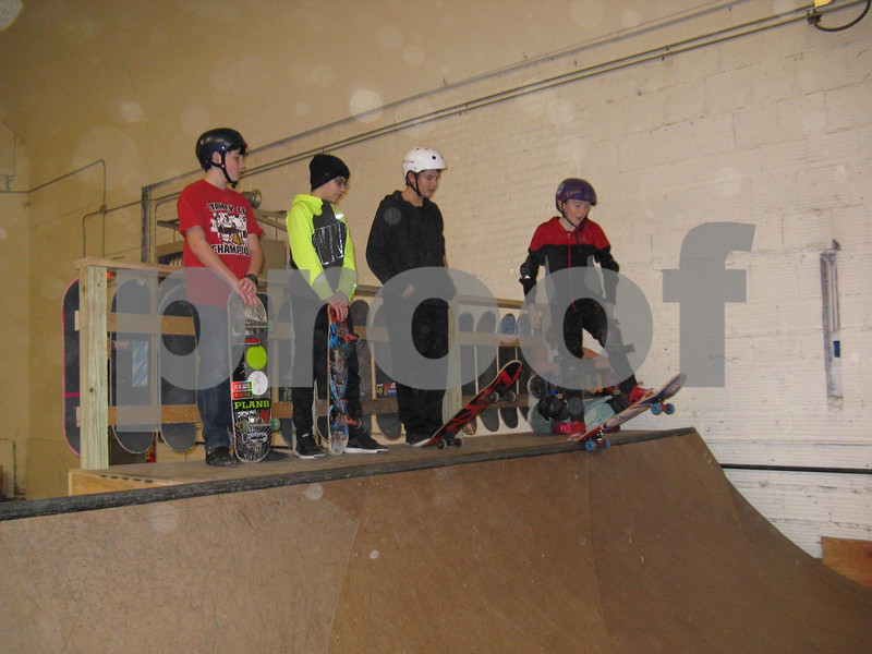 Kids wait their turn to skate down the ramp Saturday at Fargo Skateboarding indoor skate park.