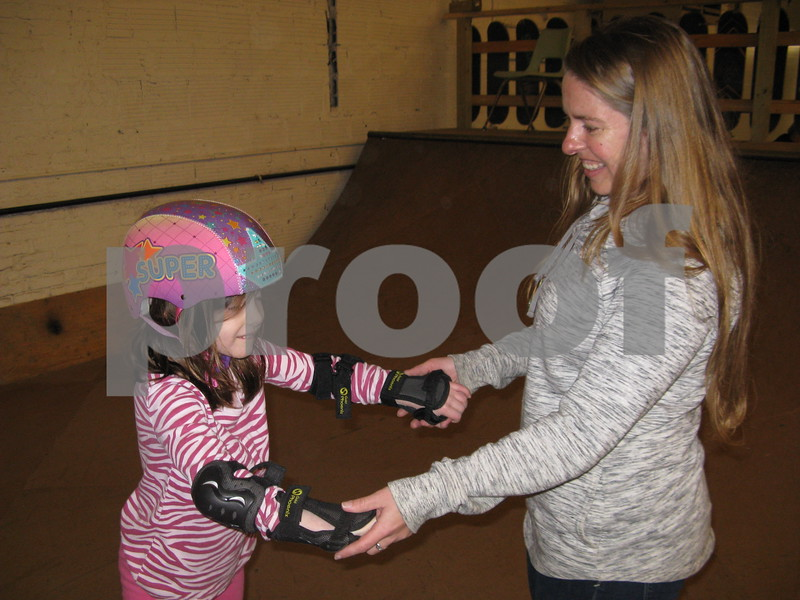 Eowyn Feldacker, 6, gets help from Fargo Skateboarding owner Ariel Ries on Saturday.