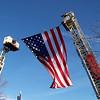 Carol Harper - The Morning Journal <br> Two aerial trucks lift an American flag in honor of retired Elyria firefighter Mark Horton.