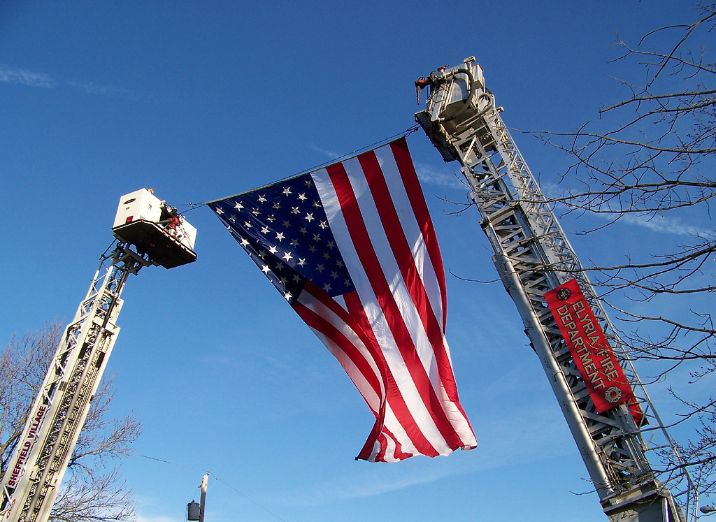 . Carol Harper - The Morning Journal <br> Two aerial trucks lift an American flag in honor of retired Elyria firefighter Mark Horton.