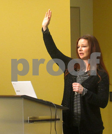 "Sarah Moses of DeKalb raises her hand Feb. 18 as she addresses the crowd at a meeting of Action Steps for America at the DeKalb Public Library. Activist groups across the country are pushing Republican congressmen with ties to President Donald Trump to hold town hall meetings, which have at times devolved into shouting matches. ""We're a nonpartisan group,"" said Moses, organizer of Action Steps for America. ""Everyone here is against dangerous policies for the U.S."""