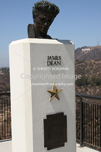 "James Dean bust at the Griffith Park Observatory with Hollywood sign in distance.  Portions of classic movie ""Rebel Without a Cause"" starring James Dean, Natalie Wood and Sal Mineo were filmed at the observatory."
