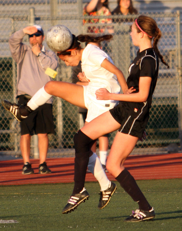 . St. Joseph\'s Marlene Palafox (12), left, passes the ball with her head before Oaks Christian\'s Allison Pantuso (4), right, can make a play during Saturday evening\'s CIF-SS Division 3 Girls\' Soccer Championship game at Warren High School in Downey, CA Saturday, March 8, 2014. (Photo by Mark Dustin for the Press Telegram)