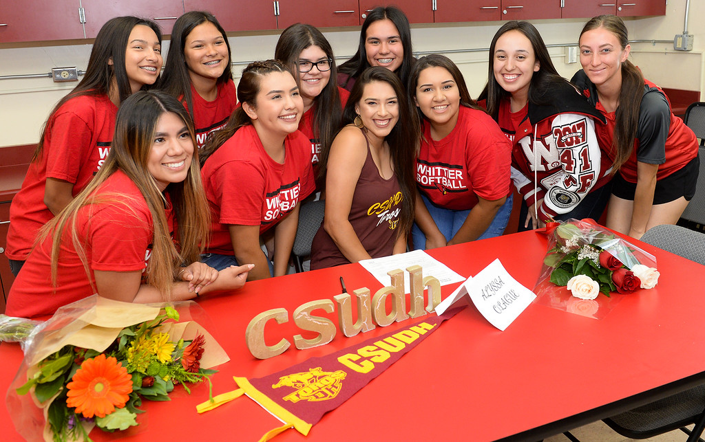 . Softball player Alyssa Olague signs her letter of intent with Cal State Dominguez Hills during a ceremony as she poses with her teammates and coach at Whittier High School in Whittier on Tuesday April 18, 2017. (Photo by Keith Durflinger/Whittier Daily News/SCNG)