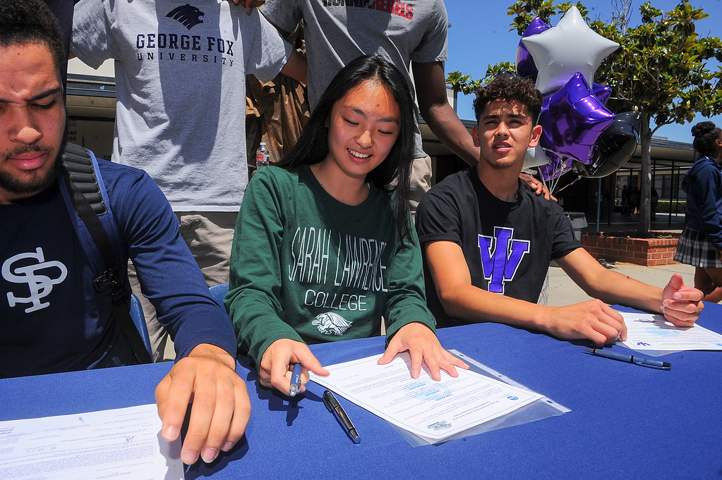 . Student athletes, from front left, Kylan Mann, Kaylin Yamada and Cody Cardenas, sign their Letters of Intent to play their sport in Universities during a lunchtime ceremony at St. Paul High School in Santa Fe Springs on Friday May 19, 2017. (Photo by Keith Durflinger/Whittier Daily News/SCNG)