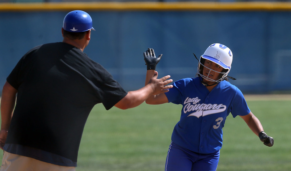 . Beaumont\'s Mahkenzy Lewis (3), right, high fives Third Base Coach Tony Barrera, left, as she rounds third base after hitting a home run during Tuesday afternoon\'s CIF-SS Division 4 softball second-round playoff game between Beaumont High School and Whittier High School at Beaumont High School in Cherry Valley, CA Tuesday, May 23, 2017. (Photo by Mark Dustin for the Press Enterprise/SCNG)