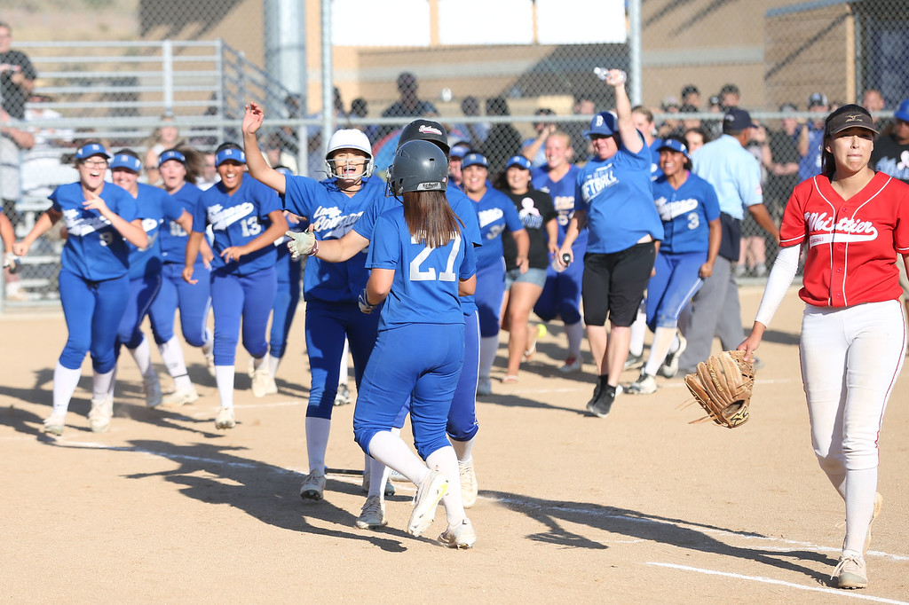 . Beaumont players and coaches rush to congratulate Megan Watkins (27), center, after she drove in the winning run in the bottom of th eseventh inning in Tuesday afternoon\'s CIF-SS Division 4 softball second-round playoff game between Beaumont High School and Whittier High School at Beaumont High School in Cherry Valley, CA Tuesday, May 23, 2017. (Photo by Mark Dustin for the Press Enterprise/SCNG)