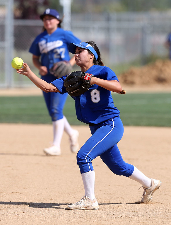 . Beaumont\'s Mikayla Mendoza (8), bottom, throws out a runner at first base as Megan Watkins (27), top, looks on during Tuesday afternoon\'s CIF-SS Division 4 softball second-round playoff game between Beaumont High School and Whittier High School at Beaumont High School in Cherry Valley, CA Tuesday, May 23, 2017. (Photo by Mark Dustin for the Press Enterprise/SCNG)