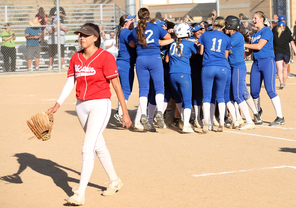 . Whittier\'s Alyssa Olague (32), left, walks off the field as Beaumont celebrates their walkoff victory in Tuesday afternoon\'s CIF-SS Division 4 softball second-round playoff game between Beaumont High School and Whittier High School at Beaumont High School in Cherry Valley, CA Tuesday, May 23, 2017. (Photo by Mark Dustin for the Press Enterprise/SCNG)