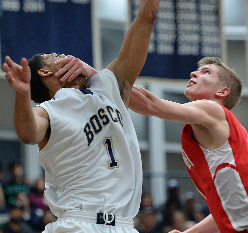 . St. John Bosco\'s Tyler Dorsey (1) takes a swat to the face under the basket from Mater Dei\'s Rex Pflueger (1) in a Trinity League boys basketball game Friday, February 07, 2014, in Bellflower, CA.   Photo by Steve McCrank/Daily Breeze