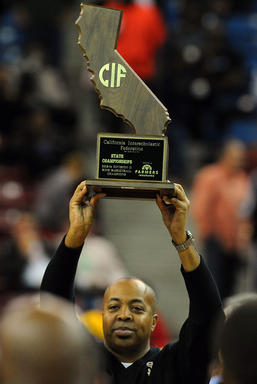 . Bosco coach Derrick Taylor holds up the state championship trophy at Sleep Train Arena in Sacramento, CA on Saturday, March 29, 2014. St. John Bosco vs Folsom in the CIF Div II boys basketball state final. 2nd half.  St. John Bosco won 63-54. (Photo by Scott Varley, Daily Breeze)