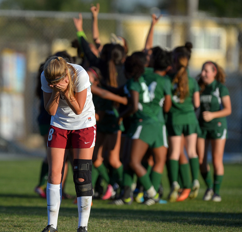 . As Poly\'s soccer team celebrates their win, Wilson\'s Katie Pratt-Thompson buries her face in her hands in disappointment in Long Beach, CA on Thursday, February 13, 2014. Long Beach Poly girls soccer beat Wilson 1-0 to capture the Moore League title.  (Photo by Scott Varley, Daily Breeze)