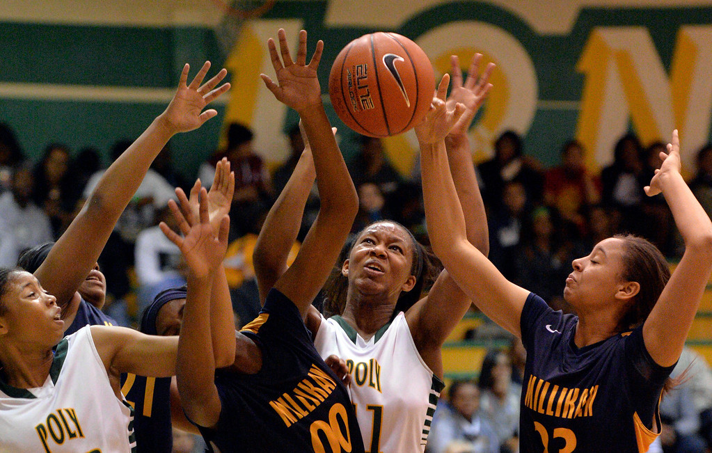 . Long Beach Poly\'s Lajahna Drummer, center, battles for a rebound with Millikan\'s Aja Wilcox, left and Esther Franks, right, in the Moore League girls basketball opener in Long Beach, CA. January 8, 2014.