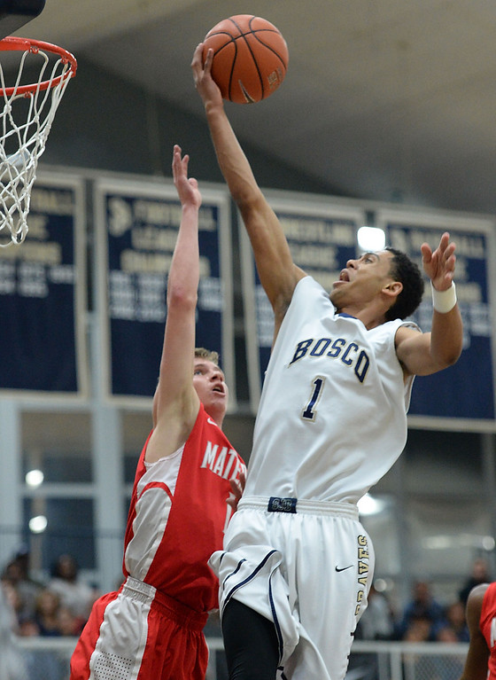 . St. John Bosco\'s Tyler Dorsey (1) delivers the ball to the bucket against Mater Dei\'s Rex Pflueger (1) in a Trinity League boys basketball game Friday, February 07, 2014, in Bellflower, CA.   Photo by Steve McCrank/Daily Breeze