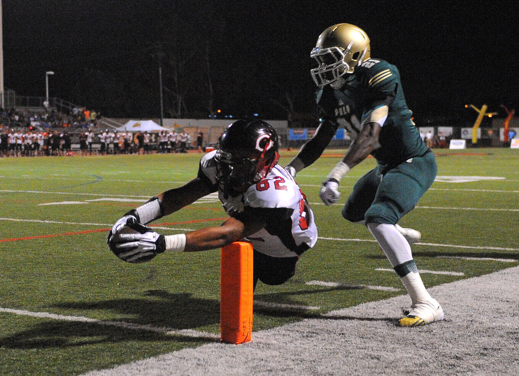 . Long Beach Poly football takes on Centennial (Corona) as part of the Mission Viejo Classic in Mission Viejo, CA on Friday, September 13, 2013. Poly\'s Jaylin McNeal watches as Centennial\'s Eric Locklin dives for a 1st qtr TD. (Photo by Scott Varley, Press-Telegram)