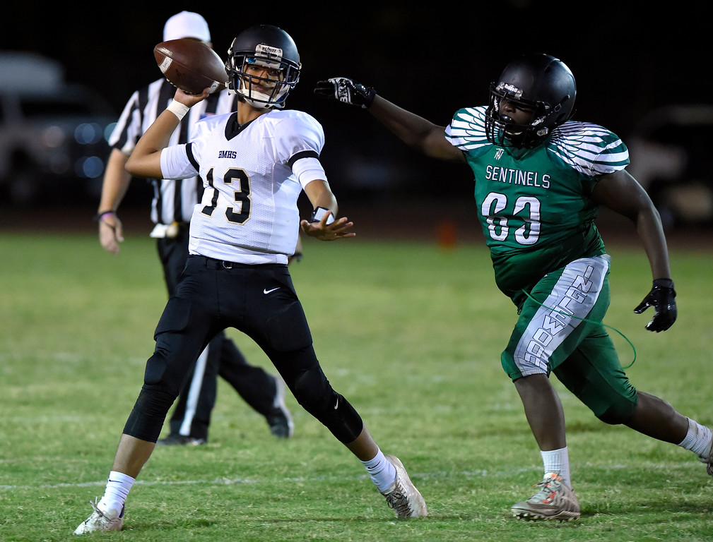 . Bishop QB Matthew Cortez gets the ball off under pressure from Inglewood��ôs Devin Ramsey in Inglewood, CA on Thursday, September 14, 2017. Bishop Montgomery vs Inglewood preseason football. (Photo by Scott Varley, Daily Breeze/SCNG)