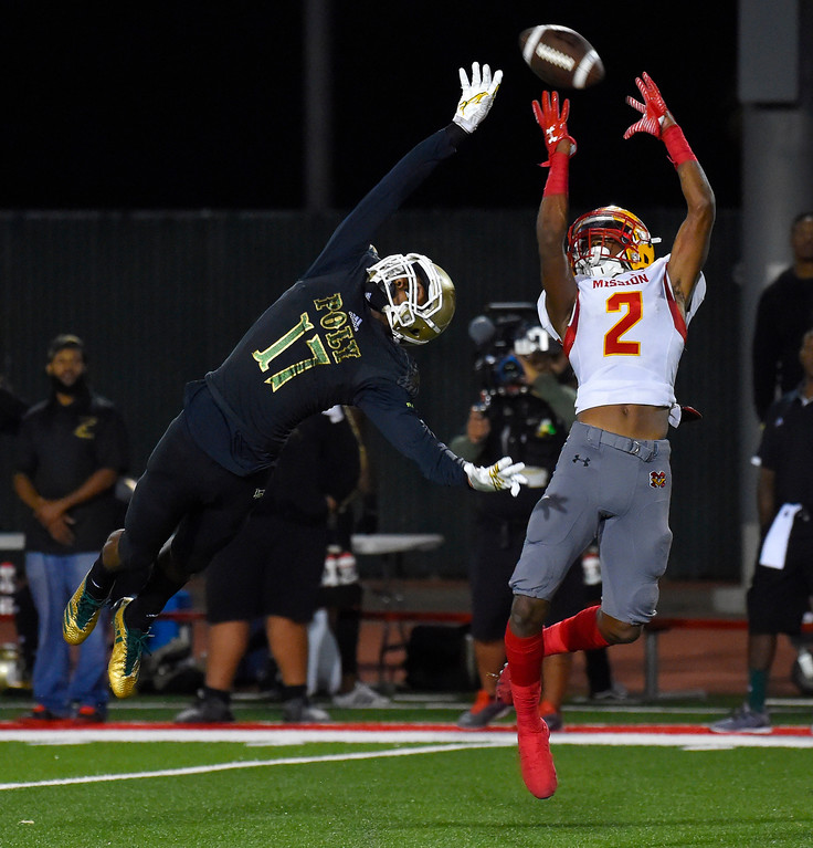 . Mission�s Olaijah Griffin, right, nearly comes up with an interception on a pass intended for Poly�s Damarjay Guy in Long Beach on Friday, September 15, 2017. Mission Viejo vs Long Beach Poly preseason football at Veterans Stadium. (Photo by Scott Varley, Press-Telegram)