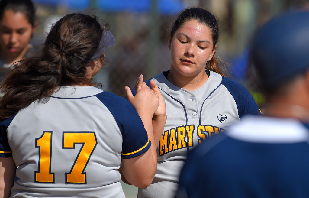 . Mary Star pitcher Alessandra Samperio, right, is high-fived by Gigi Gentile after getting out of an inning with runners on base in Long Beach on Wednesday, April 12, 2017. St. Anthony beat Mary Star 4-3. (Photo by Scott Varley, Press-Telegram/SCNG)