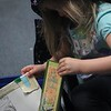 Kristi Garabrandt — The News-Herald <br> Brianna Metrick, 4, selects books from a free book bin in the library during Family Literacy Night at Longfellow Elementary School.