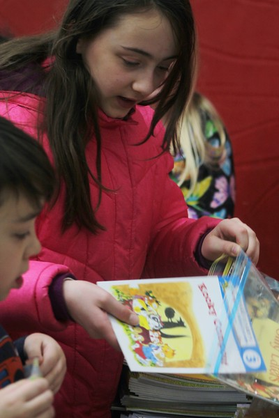 Kristi Garabrandt — The News-Herald <br> Andie Babcock along with her little brother Adam select from an assortment of books being given away to students who attended Family Literacy Night at Longfellow Elementary School.