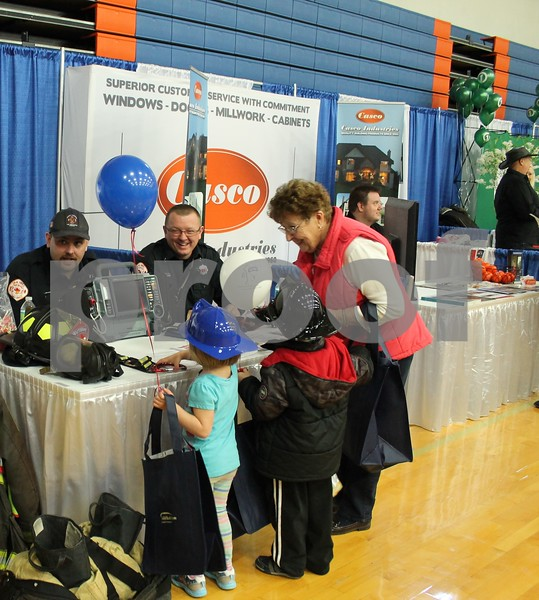 Members of the Genoa-Kingston Fire Protection District hand out prizes to Carol Cleveland and her grandchildren, of Genoa, at the Genoa Area Chamber of Commerce Home and Business Expo on Saturday at Genoa-Kingston High School.