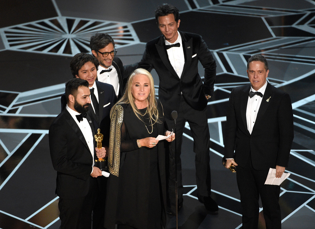 ". Darla K. Anderson, center, and from back left, Adrian Molina, Anthony Gonzalez, Gael Garcia Bernal, Benjamin Bratt, and Lee Unkrich accept the award for best animated feature film for ""Coco\"" at the Oscars on Sunday, March 4, 2018, at the Dolby Theatre in Los Angeles. (Photo by Chris Pizzello/Invision/AP)"