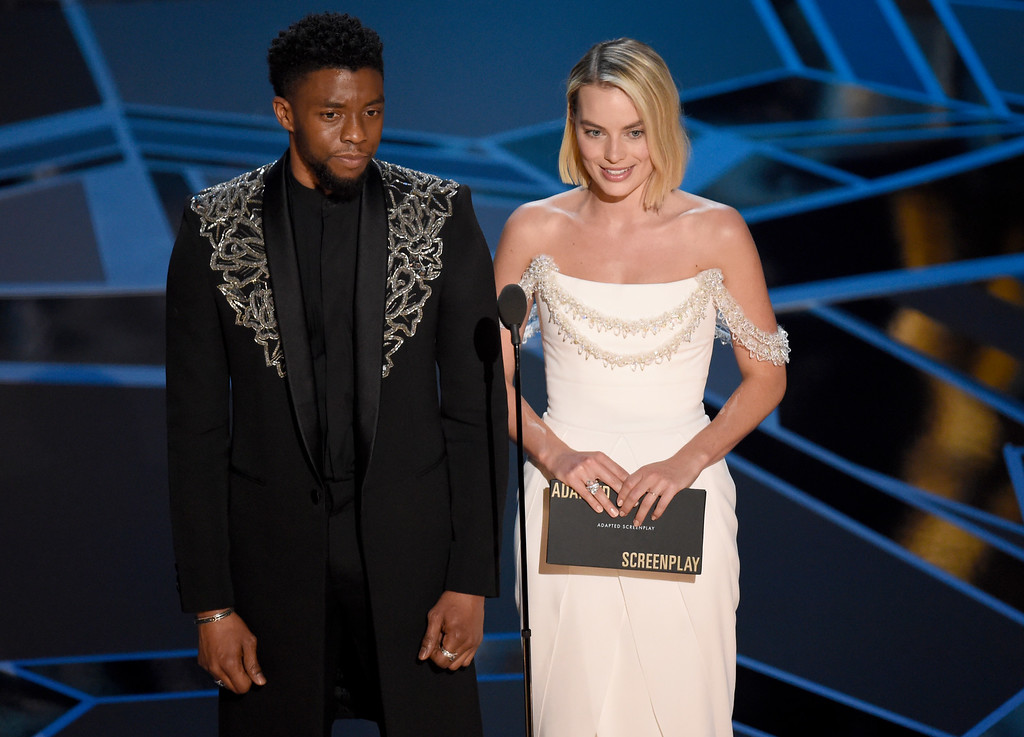 . Chadwick Boseman, left, and Margot Robbie present the award for best adapted screenplay at the Oscars on Sunday, March 4, 2018, at the Dolby Theatre in Los Angeles. (Photo by Chris Pizzello/Invision/AP)