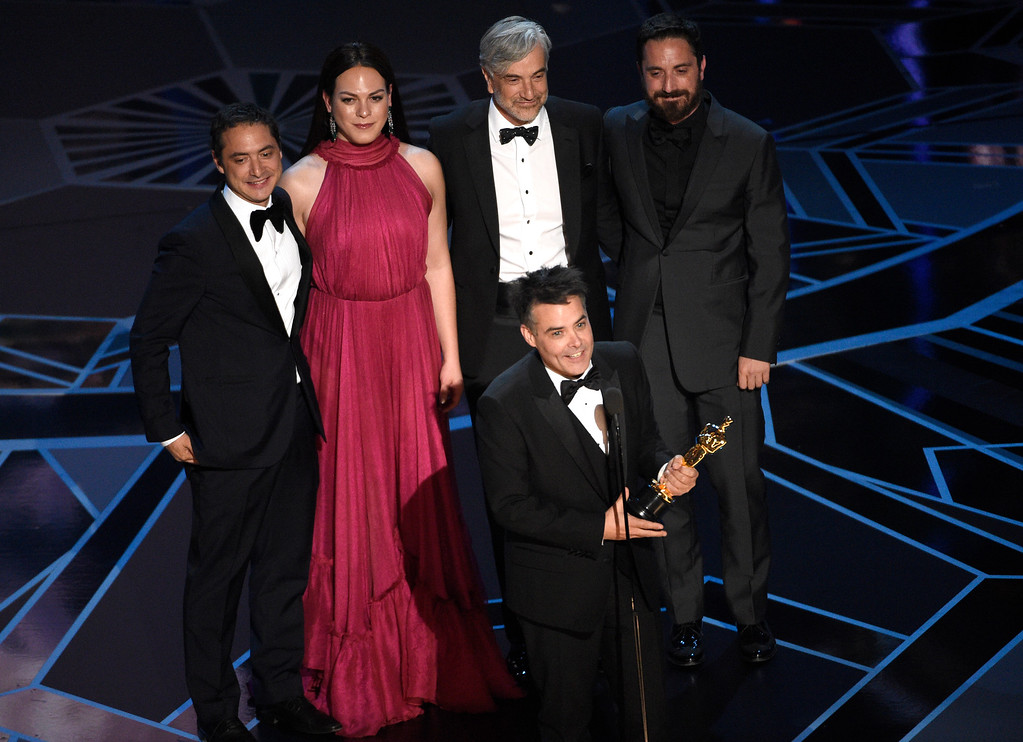 ". Sebastian Lelio, foreground center, and Nicolas Saavedra, from back left, Daniela Vega, Alejandro Goic, and Pablo Larrain accept the award for best foreign language film for ""A Fantastic Woman\"" at the Oscars on Sunday, March 4, 2018, at the Dolby Theatre in Los Angeles. (Photo by Chris Pizzello/Invision/AP)"