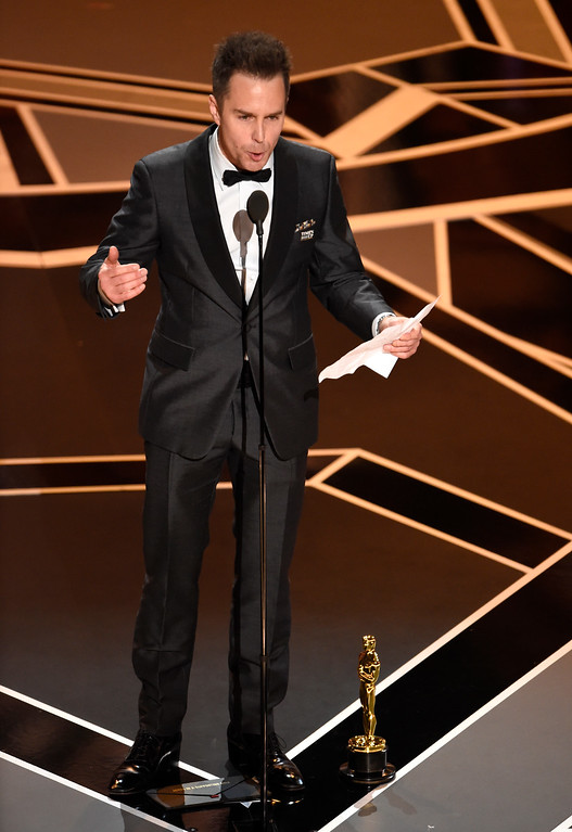 ". Sam Rockwell accepts the award for best performance by an actor in a supporting role for ""Three Billboards Outside Ebbing, Missouri\"" at the Oscars on Sunday, March 4, 2018, at the Dolby Theatre in Los Angeles. (Photo by Chris Pizzello/Invision/AP)"