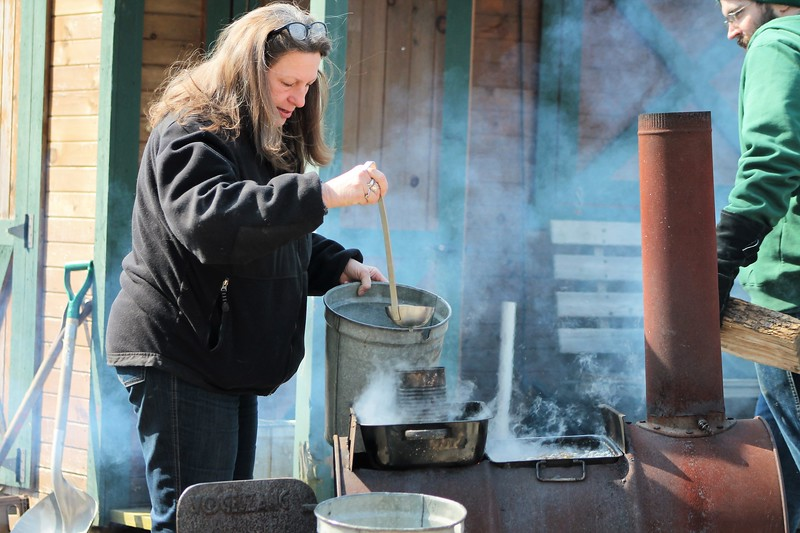 Kristi Garabrandt - The News-Herald<br /> Valerie Reinhardt horticulture education specialist at Farmpark adds more sap water to a backyard oven to make maple syrup.