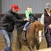Kristi Garabrandt - The News-Herald<br /> Max Gallagher 18 months, Stow, with help from his dad Tim and volunteer Jessica Slanski, 14, gets his first pony ride at the Farmpark.