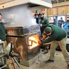 Kristi Garabrandt - The News-Herald<br /> Farmpark event manager Andy McGovern adds wood to the fire under the evaporator to raise the temperature of the sap water. Sap water has to boil seven degrees above boiling point to make it into syrup