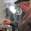 Kristi Garabrandt - The News-Herald<br /> Farmpark volunteer Gary Goodge checks the level of maple syrup in the pan.