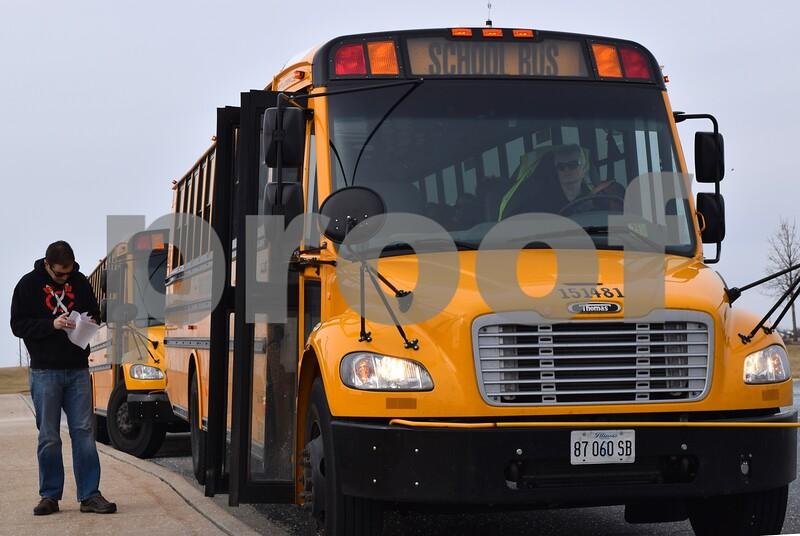 DeKalb High School Band Director Steve Lundin looks over information and a list of students one last time before boarding a school bus headed toward O'Hare International Airport in Chicago on Sunday, March 12. One hundred and two members of the DHS Marching Barbs and 11 chaperones will fly from Chicago to Ireland for an eight-day trip. The group will be joined in Ireland by 37 parents and family members who will travel separately as part of a companion trip.